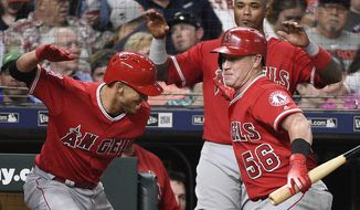 Los Angeles Angels' Andrelton Simmons, left, celebrates his three-run home run off Houston Astros relief pitcher Joe Smith with Kole Calhoun (56), as Martin Maldonado watches during the seventh inning of a baseball game Tuesday, April 24, 2018, in Houston. (AP Photo/Eric Christian Smith)