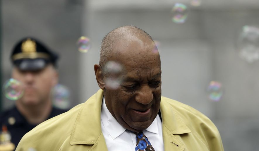 Bill Cosby departs after his sexual assault trial near a cloud of bubbles blown by a protester, Tuesday, April 24, 2018, at the Montgomery County Courthouse in Norristown, Pa. (AP Photo/Matt Slocum)