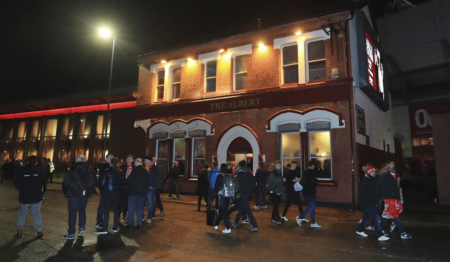 People walk past the Albert pub on Walton Breck Road, Liverpool, England after the Champions League, semifinal first leg soccer match at Anfield, Tuesday April 24, 2018. Police say a man was attacked outside the Albert pub near Anfield before the Champions League game between Liverpool and Roma on Tuesday.(Peter Byrne/PA via AP)