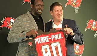 FILE - In this March 23, 2018, file photo, Buccaneers NFL football player Jason Pierre-Paul, left, poses with team general manager Jason Licht during a news conference in Tampa, Fla. The Bucs addressed pressing needs to improve an anemic pass rush and bolster depth on the defensive line by trading for Jason Pierre-Paul and signing Beau Allen and Vinny Curry in free agency.  Nevertheless, Licht still has some holes to fill if Jameis Winston is going to lead the Bucs to their first playoff berth in over a decade. (Greg Auman/The Tampa Bay Times via AP, File)