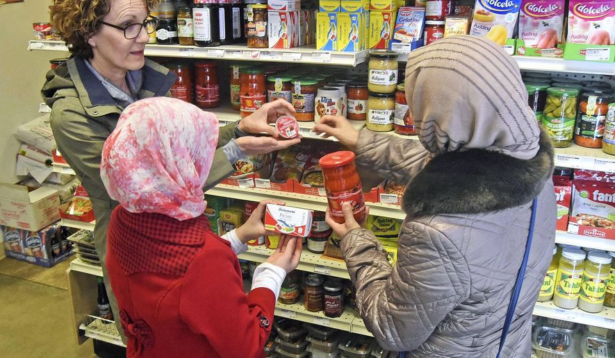 In this April 21, 2018, photo, Lisa Kadlec, left, helps two Amiri family members shop for cooking supplies for an upcoming community meal in Bismarck, N.D.  The family, who came to Bismarck from Pakistan in 2016, are originally from Afghanistan. Because they received support from local community members, the family will be giving back by cooking a traditional Afghan meal on May 4 at the United Church of Christ. (Tom Stromme/The Bismarck Tribune via AP)