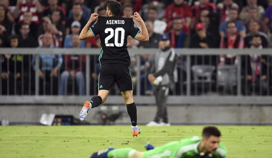 Madrid's Marco Asensio, top, celebrates after scoring his side's second goal during the soccer Champions League first leg semifinal soccer match between FC Bayern Munich and Real Madrid in Munich, southern Germany, Wednesday, April 25, 2018. (Andreas Gebert/dpa via AP)