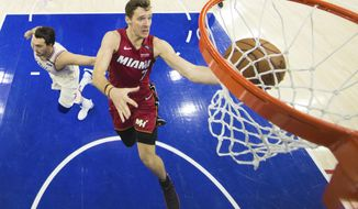 Miami Heat's Goran Dragic, right, of Slovenia, shoots as he gets past Philadelphia 76ers' Dario Saric, left, of Croatia, during the second half in Game 5 of a first-round NBA basketball playoff series, Tuesday, April 24, 2018, in Philadelphia. The 76ers won 104-91. (AP Photo/Chris Szagola)