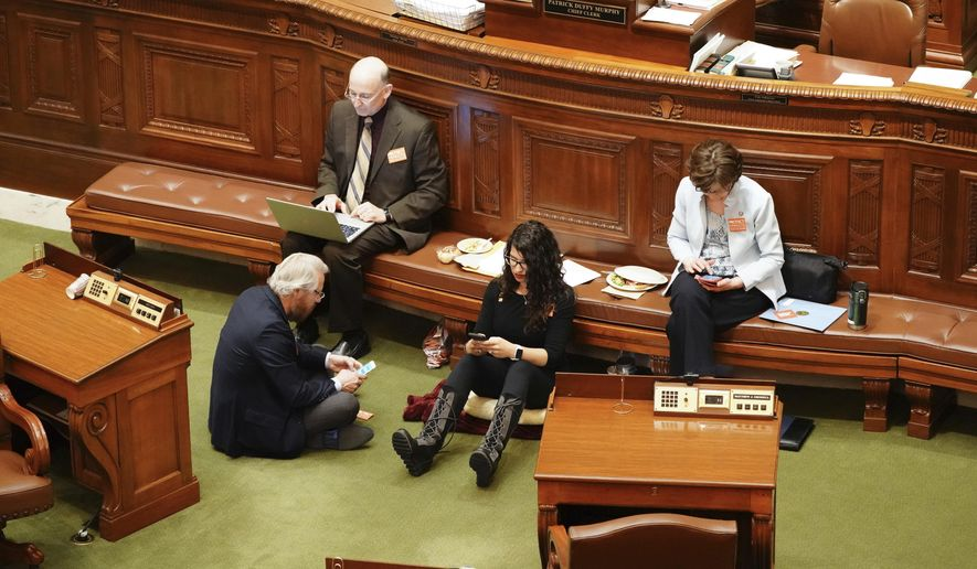 State Rep. Erin Maye Quade, of Apple Valley, second from right, holds a 24-hour sit-in on the Minnesota House floor for stronger gun laws, Tuesday, April 24, 2018, in St. Paul, Minn., joined by fellow Democratic-Farmer-Labor Party Reps. Raymond Dehn, Minneapolis, seated on floor; Peter Fischer, Maplewood, and JoAnn Ward, Woodbury. (Glen Stubbe/Star Tribune via AP)
