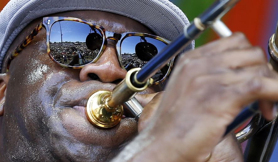 FILE - In this April 23, 2016 file photo, The crowd is reflected in the sunglasses of Big Sam, of Big Sam's Funky Nation, as he performs at the New Orleans Jazz and Heritage Festival in New Orleans.  Music lovers are converging this week on the Crescent City for the festival, which takes place over two weekends starting on Friday, April 27, 2018, featuring out-of-town artists such as Rod Stewart and Sting, as well as performers from across New Orleans and Louisiana.  (AP Photo/Gerald Herbert, File)