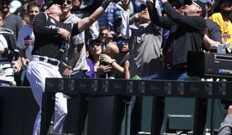 Colorado Rockies third baseman Ryan McMahon, less a pop foul off the bat of San Diego Padres' Wil Myers to a fan in the first inning of a baseball game Wednesday, April 25, 2018, in Denver. (AP Photo/David Zalubowski)