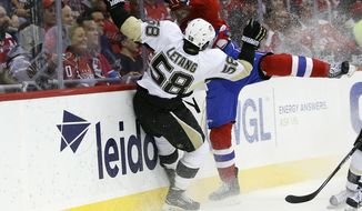 FILE - In this April 7, 2016, file photo, Pittsburgh Penguins defenseman Kris Letang (58) and Washington Capitals right wing T.J. Oshie (77) collide against the boards in the first period of an NHL hockey game, in Washington. Like tourists flocking to see the cherry blossoms in full bloom, the Pittsburgh Penguins making a trip to Washington for the playoffs has become a rite of spring. (AP Photo/Alex Brandon, File)