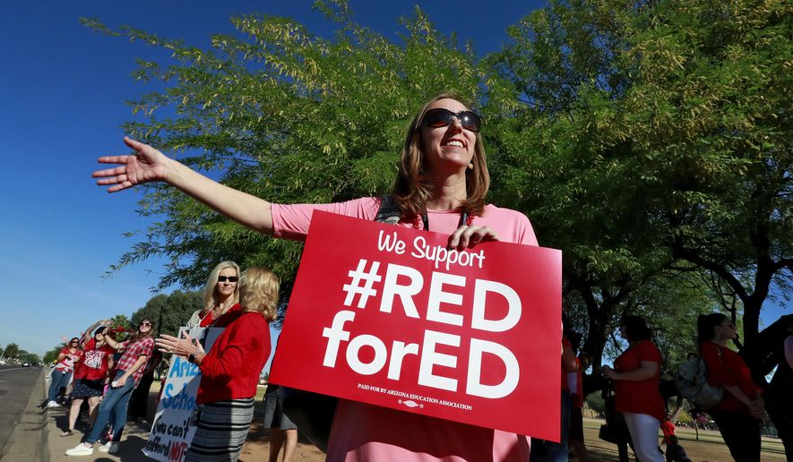 Highland Arts Elementary School kindergarten teacher Melissa Perez participates in a final walk-in Wednesday, April 25, 2018, in Mesa, Ariz. Communities and school districts are preparing for a historic statewide teacher walkout on Thursday that could keep hundreds of thousands of students out of school indefinitely. (AP Photo/Matt York)