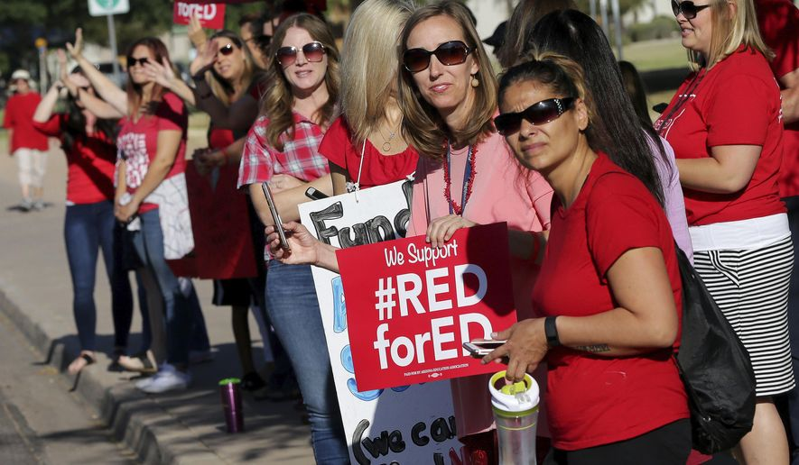 Teachers from Highland Arts Elementary School stage a final walk-in Wednesday, April 25, 2018, in Mesa, Ariz. Communities and school districts are preparing for a historic statewide teacher walkout on Thursday that could keep hundreds of thousands of students out of school indefinitely. (AP Photo/Matt York)