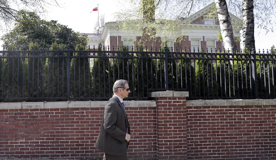Nikolay V. Pukalov, head of the Counsular Division of the Embassy of the Russian Federation of Washington, D.C., walks past the brick and iron fencing surrounding the former Russian consul general's residence, where the Russian flag continue to fly, Wednesday, April 25, 2018, in Seattle. Officials with the U.S. State Department have drilled out locks to access and inspect the home, a day after Russian staff vacated the site. President Donald Trump's administration announced last month that the diplomatic outpost would be closed and 60 Russian diplomats would be expelled nationwide to punish Moscow for its alleged role in poisoning an ex-spy in Britain. (AP Photo/Elaine Thompson)