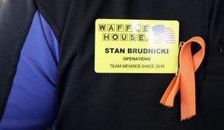 Waffle House employee Stan Brudnicki wears a ribbon on his uniform to honor shooting victims Wednesday, April 25, 2018, in Nashville, Tenn. The restaurant re-opened Wednesday after four people were killed by a gunman Sunday. (AP Photo/Mark Humphrey)
