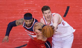 Toronto Raptors center Jakob Poeltl, right, competes for the ball against Washington Wizards forward Mike Scott (30) during the second half of Game 5 of an NBA basketball first-round playoff series Wednesday, April 25, 2018, in Toronto. (Nathan Denette/The Canadian Press via AP)