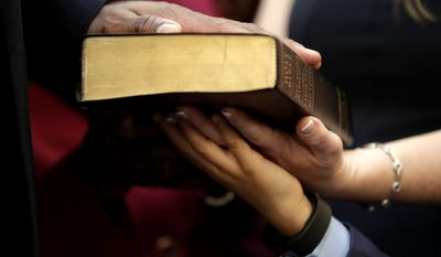 The hand of Troy Singleton, top, D-Moorestown, N.J. is seen with those of his family members on a bible as he is sworn into to the New Jersey Senate, Tuesday, Jan. 9, 2018, in Trenton, N.J. (AP Photo/Julio Cortez)