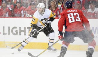 Pittsburgh Penguins right wing Phil Kessel (81) skates with the puck as is shavings are sprayed, while Washington Capitals center Jay Beagle (83) watches during the first period of Game 1 of an NHL hockey second-round playoff series Thursday, April 26, 2018, in Washington. (AP Photo/Nick Wass)