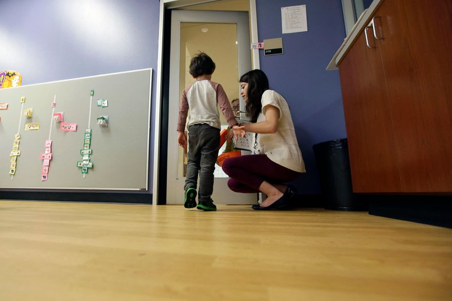Megan Krail helps a 4-year-old boy with Autism Spectrum Disorder practice trick-or-treating at The University of Texas at Dallas' Callier Center for Communication Disorders preschool class in Dallas. According to a report by the Centers for Disease Control and Prevention released on Thursday, April 26, 2018, the estimate of how common autism is again going up slightly, after seeming to level off for a couple of years. (AP Photo/LM Otero)