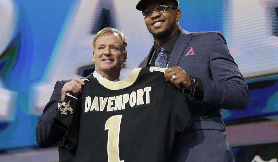 CORRECTS THAT DAVENPORT PLAYED AT UTSA, INSTEAD OF UTEP - NFL Commissioner Roger Goodell, left, presents UTSA's Marcus Davenport with his New Orleans Saints jersey during the first round of the NFL football draft Thursday, April 26, 2018, in Arlington, Texas. (AP Photo/David J. Phillip)