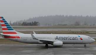 FILE- In this April 13, 2018, file photo, an American Airlines plane taxis Friday, April 13, 2018, at the Seattle-Tacoma International Airport in Seattle. American Airlines reports earns on Thursday, April 26. (AP Photo/Ted S. Warren, File)