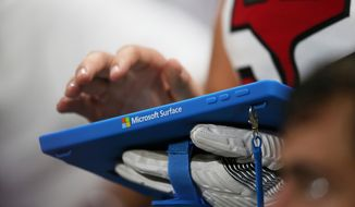 FILE- In this Aug. 31, 2017, file photo, a Microsoft Surface tablet is used during the second half of an NFL football game between the Atlanta Falcons and the Jacksonville Jaguars in Atlanta. Microsoft Corp. reports earns on Thursday, April 26, 2018. (AP Photo/John Bazemore, File)