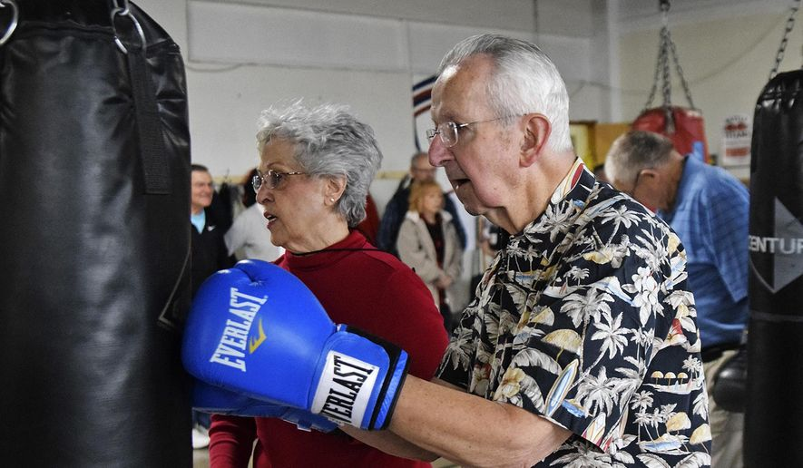 In this April 14, 2018, photo, Melvin Siverly hits the bag during the Rock Steady Boxing workout at the Weinberg Arcade in Galesburg, Ill. The class helps build strength, coordination and balance for people with Parkinson's disease. (Bill Nice/The Register-Mail via AP)