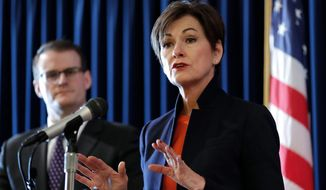 FILE - In this Jan. 8, 2018 file photo, Iowa Gov. Kim Reynolds speaks during a news conference as acting Lt. Gov. Adam Gregg, left, looks on during the opening day of the Iowa Legislature at the Statehouse in Des Moines, Iowa. An agency director fired by Reynolds had been accused of harassing female employees for years by routinely making crude sexual comments and pressuring one to go into his hotel room during work travel. Bowing to pressure after keeping the document secret for a month, the governor released a March 21 letter to her that laid out detailed allegations against Iowa Finance Authority Director Dave Jamison. The woman said Jamison talked about her breasts and constantly made sexual remarks. (AP Photo/Charlie Neibergall, File)