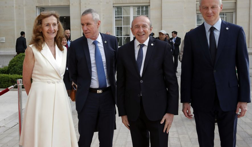 French Interior Minister Gerard Collomb, third left, Justice Minister Nicole Belloubet, left, French prosecutor in charge of terrorism Francois Molins, second left, and French Economy Minister Bruno Le Maire welcome international delegations for a conference to discuss ways to combat financing for the Islamic State group and Al-Qaida, at the OECD headquarters in Paris, Thursday, April 26, 2018. The initiative was launched by French President Emmanuel Macron to coordinate efforts to reduce the terror threat in the long term. (Philippe Wojazer, Pool via AP)