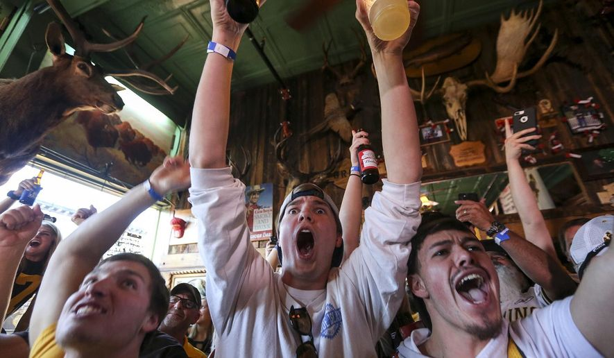 Travis Anusavice, center, cheers with other fans at a bar in Laramie, Wyo., after former Wyoming quarterback Josh Allen was selected by the Buffalo Bills in the NFL football draft, Thursday, April 26, 2018. (Josh Galemore/The Casper Star-Tribune via AP)