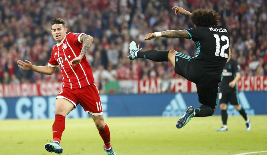 Real Madrid's Marcelo, right, is airborne beside Bayern's James during the semifinal first leg soccer match between FC Bayern Munich and Real Madrid at the Allianz Arena stadium in Munich, Germany, Wednesday, April 25, 2018. (AP Photo/Matthias Schrader)