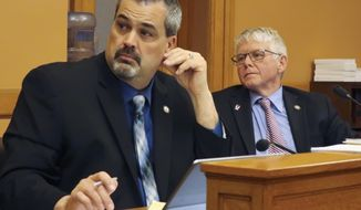 Kansas state Sens. Richard Hilderbrand, left, R-Galena, and Mike Petersen, right, R-Wichita, follow a discussion among fellow GOP senators during a meeting, Thursday, April 26, 2018, at the Statehouse in Topeka, Kan. Legislators are thinking about cutting income taxes again after raising them in 2017 to address persistent budget woes. (AP Photo/John Hanna)