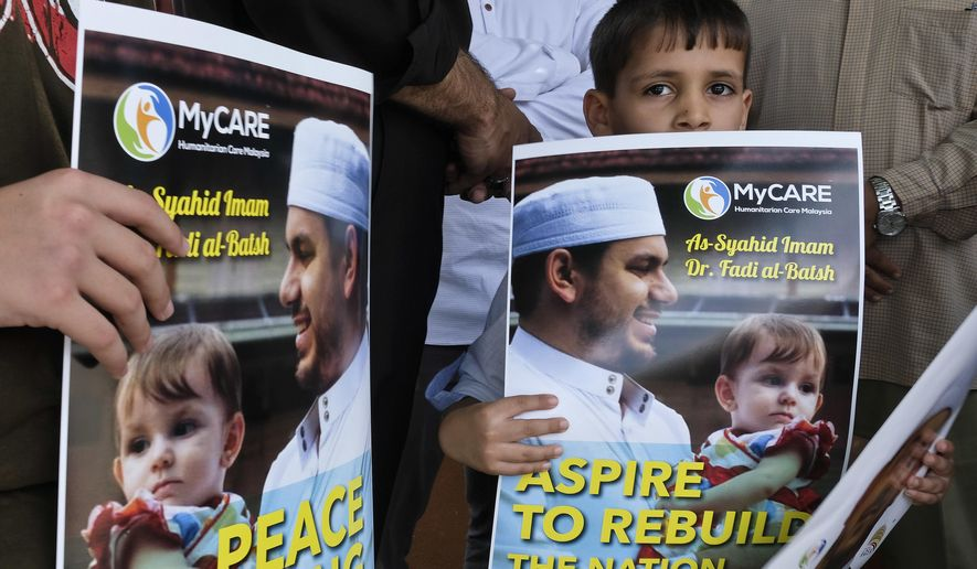 A kid holds a poster of Palestinian Fadi al-Batsh portrait at a mosque in Selayang, on the outskirt of Kuala Lumpur, Malaysia, Wednesday, April 25, 2018. The Palestinian envoy in Malaysia says the body of the Hamas militant killed last week in Kuala Lumpur will be repatriated to the Gaza Strip for burial. Fadi al-Batsh, an electrical engineering lecturer at a Malaysian university, was gunned down by two men on a motorcycle as he was on his way to a mosque early Saturday. (AP Photo/Sadiq Asyraf)