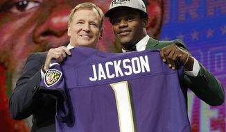 Commissioner Roger Goodell, left, presents Louisville's Lamar Jackson with his Baltimore Ravens jersey during the first round of the NFL football draft, Thursday, April 26, 2018, in Arlington, Texas. (AP Photo/David J. Phillip)