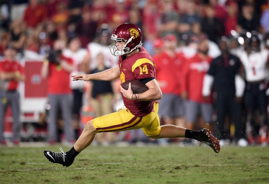 FILE - In this Oct. 14, 2017, file photo, Southern California quarterback Sam Darnold (14) runs with the ball during the second half of an NCAA college football game against Utah, in Los Angeles. Darnold is expected to be a first round pick in the NFL Draft. (AP Photo/Kelvin Kuo, File)