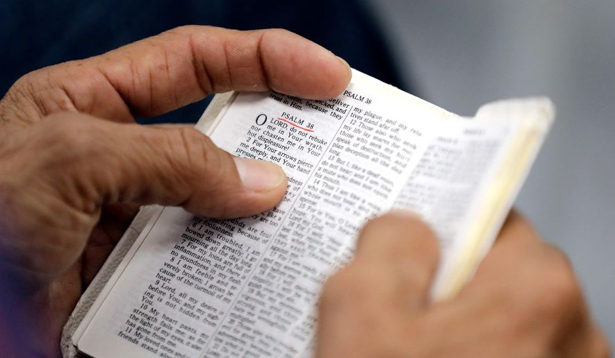 FILE- In this Sept. 3, 2017, file photo, a man holds a bible during service at Christ United Church in the aftermath of Hurricane Harvey in Cypress, Texas. Bible sales would not be banned in California under proposed state legislation, contrary to widely shared claims by multiple online sites. (AP Photo/David J. Phillip, File)