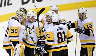 Pittsburgh Penguins goaltender Matt Murray (30) celebrates with right wing Patric Hornqvist (72), of Sweden; right wing Phil Kessel (81); center Dominik Simon (12); and others after Game 1 of an NHL second-round hockey playoff series against the Washington Capitals, Thursday, April 26, 2018, in Washington. The Penguins won 3-2. (AP Photo/Nick Wass)