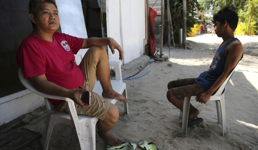 Filipino cook Marlon Laguna, left, sits outside their closed beachfront restaurant as the government implements the temporary closure of the country's most famous beach resort island of Boracay, in central Aklan province, Philippines, on Thursday, April 26, 2018. Many workers in the island are now jobless as Boracay, famed for its white-sand beaches, closes for up to six months to recover from overcrowding and development. (AP Photo/Aaron Favila)