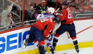 FILE - In this May 13, 2013, file photo, New York Rangers right wing Ryan Callahan (24) gets checked into the boards by Washington Capitals left wing Alex Ovechkin (8), from Russia, and Steve Oleksy during the second period of Game 7 of a first-round NHL Stanley Cup playoff hockey series in Washington. 2013 was the third year in a row the two teams met in the playoffs. (AP Photo/Nick Wass, File)