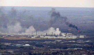 This image from video provided by WDIO-TV in Duluth shows smoke rising from the Husky Energy oil refinery after an explosion Thursday morning, April 26, 2018, in Superior, Wis. Authorities say several people were injured in the explosion. (WDIO-TV via AP)