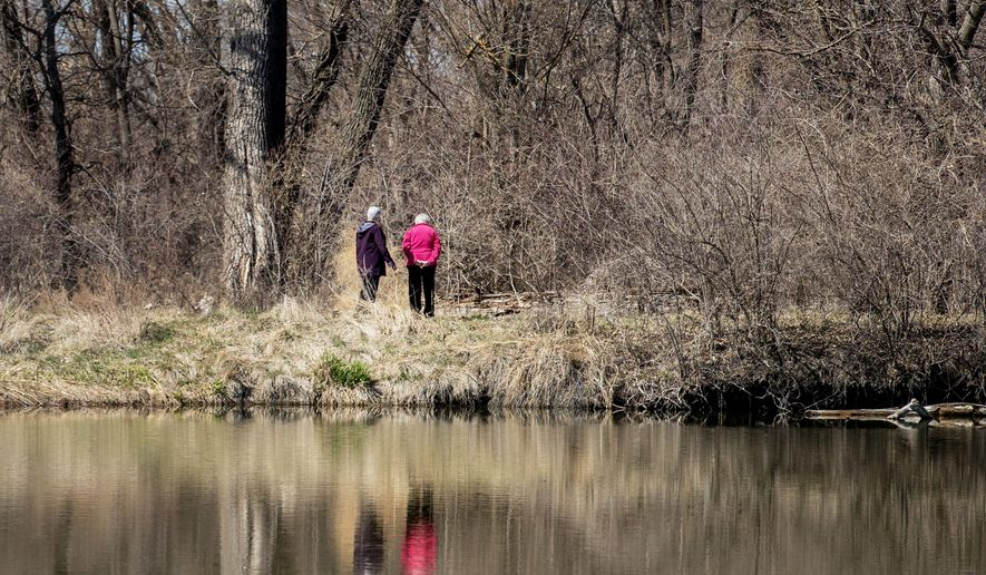 In this Thursday April 19, 2018 photo, Sister Margaret Mary Hinz, left, and Sister Catherine Kuper walk alongside a pond on land owned by The Sisters of Mercy in Waterloo, Neb. The religious order has granted a conservation easement that will protect the pond and 22 acres of land around it from development that could harm the wildlife habitat or solitude. (Chris Machian/Omaha World-Herald via AP)