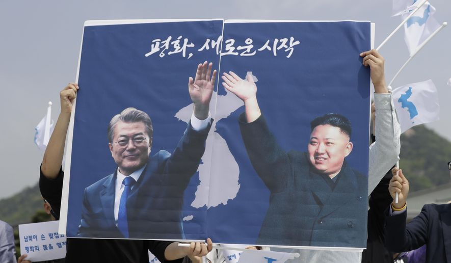 South Koreans hold a banner showing the pictures of South Korean President Moon Jae-in, left, and North Korean leader Kim Jong-un to welcome the planned summit between South and North Koreas near the presidential Blue House in Seoul, South Korea, Thursday, April 26, 2018. (AP Photo/Lee Jin-man)