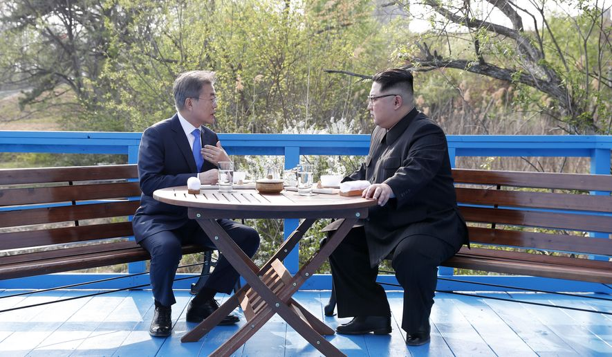 North Korean leader Kim Jong-un, right, and South Korean President Moon Jae-in talk at the border village of Panmunjom in the Demilitarized Zone, South Korea, Friday, April 27, 2018. North Korean leader Kim made history by crossing over the world's most heavily armed border to greet South Korean President Moon for talks on North Korea's nuclear weapons. (Korea Summit Press Pool via AP)
