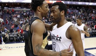 Toronto Raptors guard DeMar DeRozan, left, talks with Washington Wizards guard John Wall (2) after Game 6 of an NBA basketball first-round playoff series Friday, April 27, 2018, in Washington. The Raptors won 102-92, and won the series. (AP Photo/Alex Brandon)