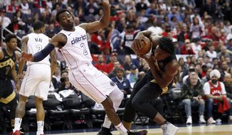 Washington Wizards guard John Wall (2) fouls Toronto Raptors forward OG Anunoby, right, during the first half of Game 6 of an NBA basketball first-round playoff series Friday, April 27, 2018, in Washington. (AP Photo/Alex Brandon)