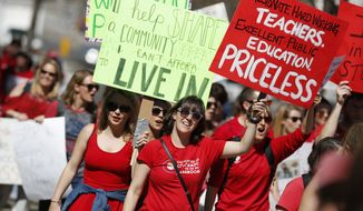 Teachers march during a rally, Friday, April 27, 2018, in Denver. More than 10,000 teachers from more than 20 districts scattered across Colorado are demonstrating as part of a burgeoning teacher uprising from the East to the interior West that is demanding more tax dollars be spent in public schools. (AP Photo/David Zalubowski)