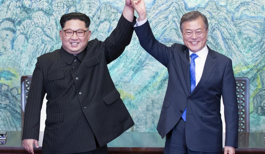 North Korean leader Kim Jong Un, left, and South Korean President Moon Jae-in raise their hands after signing on a joint statement at the border village of Panmunjom in the Demilitarized Zone, South Korea, Friday, April 27, 2018. (Korea Summit Press Pool via AP)