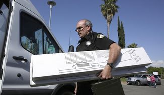 John Lopes, a crime scene investigator for the Sacramento Sheriff's office, carries boxes of evidence taken from the home of murder suspect Joseph DeAngelo to a sheriff's vehicle Thursday, April 26, 2018, in Citrus Heights, Calif. DeAngelo, 72, was taken into custody Tuesday on suspicion of committing multiple homicides and rapes in the 1970s and 1980s in California. Authorities spent the day going through the home for evidence. (AP Photo/Rich Pedroncelli)