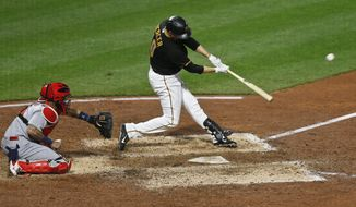 Pittsburgh Pirates' Jordy Mercer hits a two-run triple in front of St. Louis Cardinals catcher Yadier Molina during the ninth inning of a baseball game Friday, April 27, 2018, in Pittsburgh. (AP Photo/Keith Srakocic)