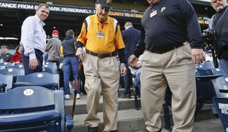 Phil Coyne, center, an usher for the Pittsburgh Pirates for more than 70 years, is assisted to the field for a celebration of his 100th birthday at PNC Park, before a baseball game between the Pirates and the St. Louis Cardinals, Friday, April 27, 2018, in Pittsburgh. Coyne retired earlier this year.(AP Photo/Keith Srakocic)