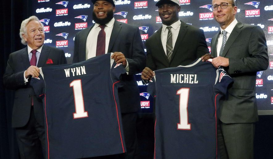 New England Patriots NFL football team owner Robert Kraft, left, and his son, team president Jonathan Kraft, right, pose with first-round NFL draft picks, offensive lineman Isaiah Wynn second from left, and running back Sony Michel, second from right, both out of the University of Georgia, Friday, April 27, 2018, in Foxborough, Mass. (AP Photo/Bill Sikes)