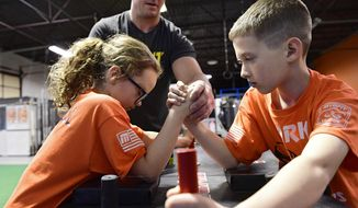 Aidan Cornell, 10, from Jackson Township, Pa., battles his sister Grace at a York Armfighters practice on April 10, 2018. The Armfighters, from York, Pa., are a youth arm wrestling club team that is a member of the Myofit Junior Armfighter league. The team is hoping to compete in a junior nationals event in Orlando in November.    (Maddie Crocenzi/York Daily Record via AP)
