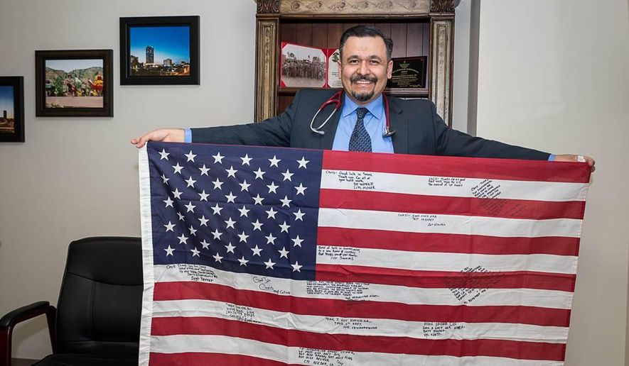 This photo taken April 18, 2018, shows a U.S. flag, signed by members of a marine platoon in Iraq in 2008, is behind on the family of Dr. Mohammed Aldeen among his treasured possessions. (Shaie Williams /The Amarillo Globe News via AP)