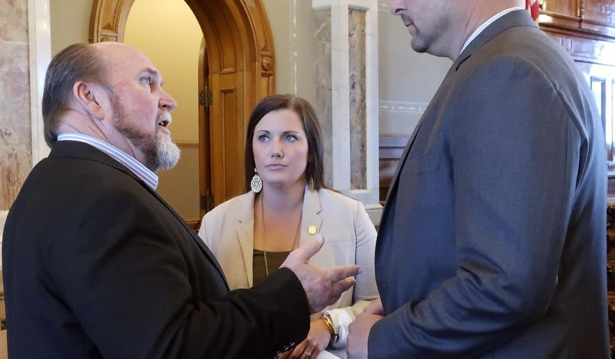 Kansas state Rep. Joe Seiwert, left, R-Pretty Prairie, confers with House Speaker Ron Ryckman Jr., right, R-Olathe, as Ryckman's chief of staff, Paje Resner, center, watches, Friday, April 27, 2018, at the Statehouse in Topeka, Kan. Lawmakers are considering budget measures and tax cuts. (AP Photo/John Hanna)